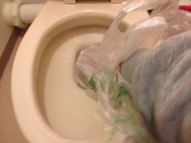 手にビニール袋をまいてトイレの詰まりを解消